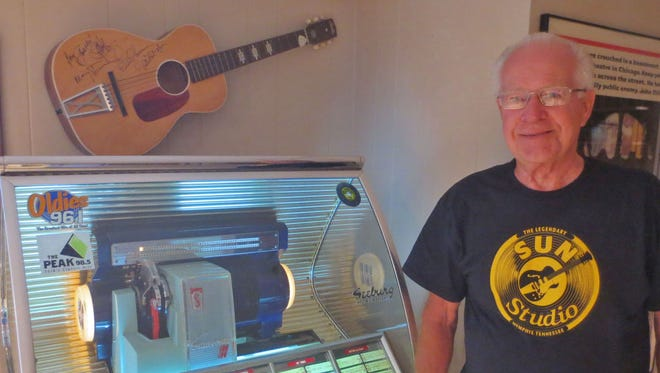 Roy Robbins stands next to his 1954 Seeburg jukebox.  On the wall is a guitar signed by Peter, Paul, and Mary during one of the trio's performances at the Strand Theatre.