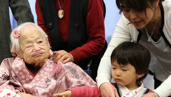 Misao Okawa, the world's oldest person, poses for a photo with a great-grandchild and grandchild at a birthday celebration the day before she turns 117.