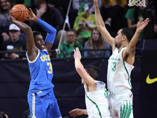 UCLA's Aaron Holiday, left, looks for an open teammate under pressure from Oregon's Payton Pritchard, center, and Paul White during the second half an NCAA college basketball game Saturday, Jan. 20, 2018, in Eugene, Ore. (AP Photo/Chris Pietsch)