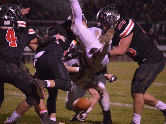 Pleasant's defense tackles Genoa's Noah Edwards during Friday night's 48-21 home win to open the Division V playoffs.