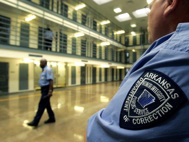 Guards patrol a cell block housing disruptive inmates