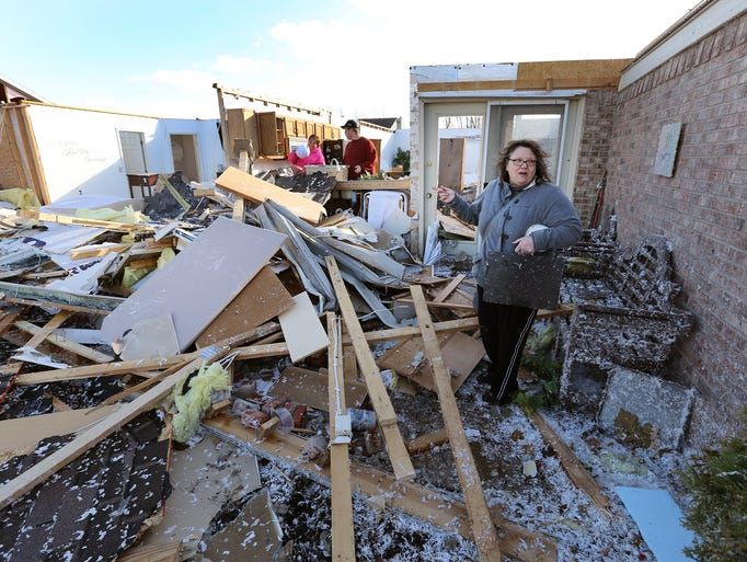 Debra Kauble searches the backyard of her home at 1540 Quail Run Drive where the roof of the home blew off and into the backyard following a tornado Sunday evening in Kokomo IN. Matt Kryger / The Star