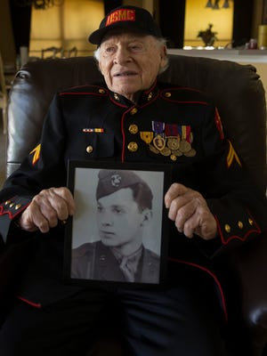 "Retired Marine Cpl. Edwin Glasberg, 92, holds a portrait of himself at 19 years old. Glasberg received two Purple Heart medals for wounds suffered in Pacific battles and a Presidential Unit Citation medal, awarded for ""extraordinary heroism in action against an armed enemy."""