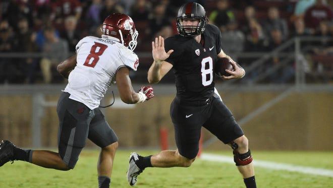 Stanford quarterback Kevin Hogan runs against Washington State linebacker Jeremiah Allison.