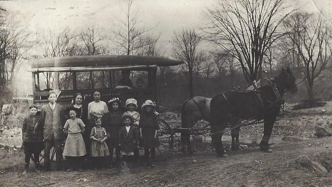 "John McDonald and other students in front of a school ""hawk"" which were farm wagons used to transport students to and from school. Local farmers were hired by the school board to provide transportation."