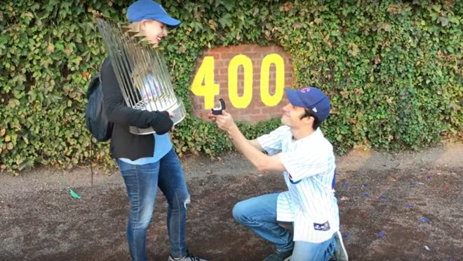 A Chicago Cubs fan proposes to his girlfriend at Wrigley Field while