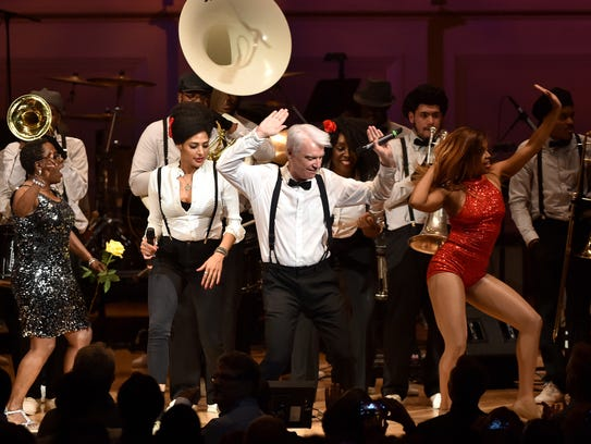 NEW YORK, NY - David Byrne performs onstage during The Music Of David Byrne & Talking Heads at Carnegie Hall on March 23, 2015 in New York City. At left, in white shirt, is Simi Stone of Woodstock, who is performing with Byrne on his current world tour, which stops at UPAC in Kingston on March 10. (Photo by Larry Busacca/Getty Images) ORG XMIT: 543489013 ORIG FILE ID: 467383622