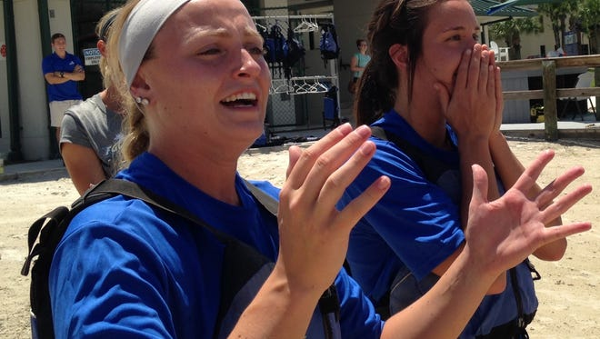 """FGCU junior Bri Innamorato, left, and senior Taylor Wade react as their """"Team Mabingwa"""" teammates go way off course in the second leg of the canoe relay race in the FGCU softball team's """"decathlon"""" for 2016."""