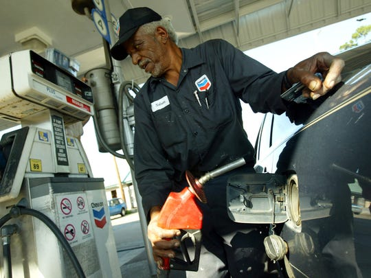 Nelson Calais fills a customer's tank at a full-service gas station.