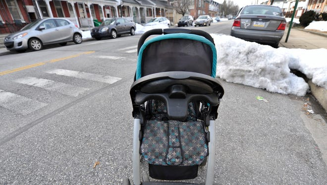 A stroller is used to hold a parking spot along Pennsylvania Avenue in York on Saturday. The city plans to begin removing trash containers, furniture and other items used to reserve parking spaces, beginning 8 a.m. Monday. The items will be treated as trash and not returned.