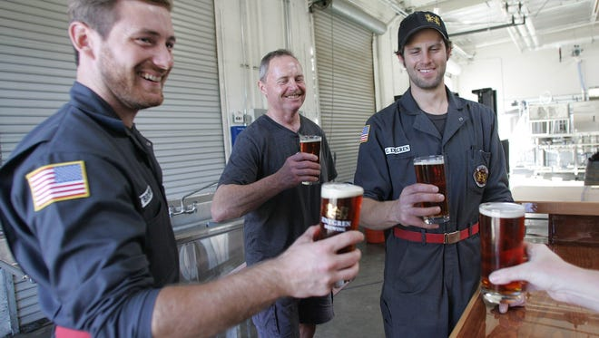 Enegren Brewing Co. co-founder Chris Enegren, right, and father-in-law David Braun, center, share a toast with Nick Brown at the craft brewery in Moorpark in a photo taken in 2015.