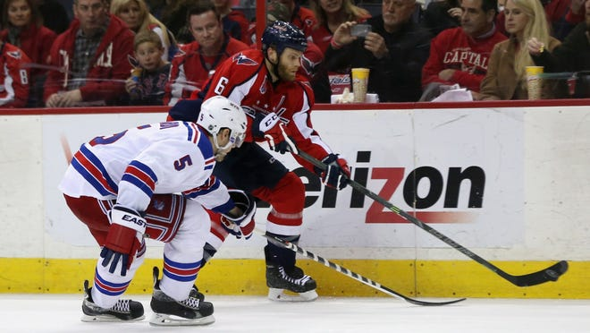 Dan Girardi of the Rangers and Tim Gleason of Washington go after the puck during the third period the Rangers 3-1 win at Verizon Center on March 11.
