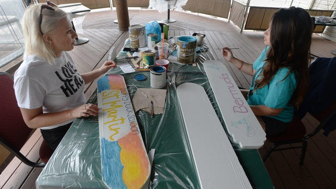 Sloppy Duck Saloon employees Kylie Kaspick, left, and Amanda Sivillo, both 23, paint signs Friday that will be be hung on new Tiki Village huts in preparation for the bar's planned opening on Friday. Restaurant owners are making changes for outdoor seating due to the COVID-19 coronavirus pandemic.