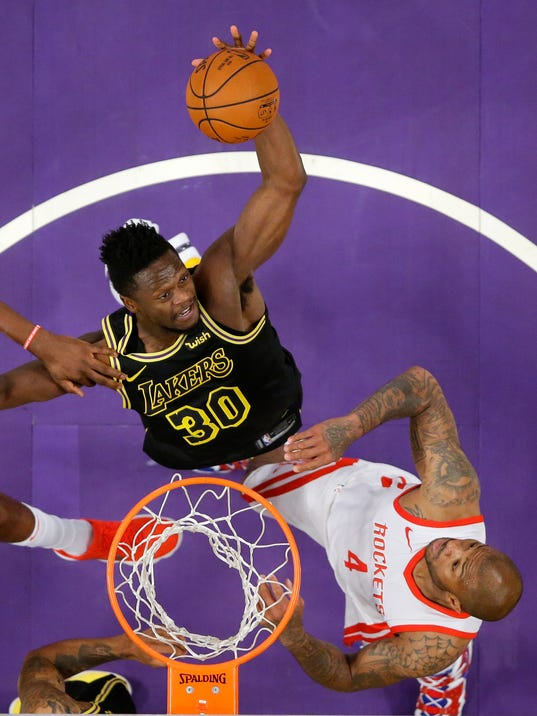 Los Angeles Lakers forward Julius Randle, top, grabs a rebound away from Houston Rockets forward PJ Tucker during the first half of an NBA basketball game Tuesday, April 10, 2018, in Los Angeles. (AP Photo/Mark J. Terrill)