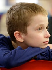 Horizon Elementary School student Noah Wallace listens to volunteers from Fox Cities Voices of Men and students from Appleton East High School during a Passport to Manhood meeting.