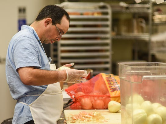Ben Nadis peels onions in the kitchen at Soul Cafe