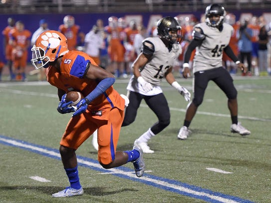 Madison Central's Cameron White (5) returns the blocked