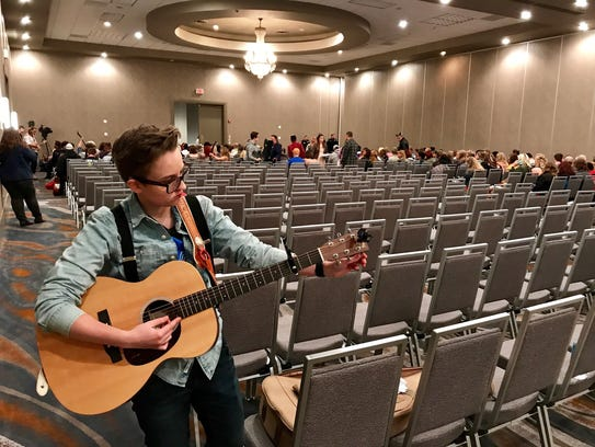 Maddie Todd, 23, of Sioux Falls, tunes her guitar at