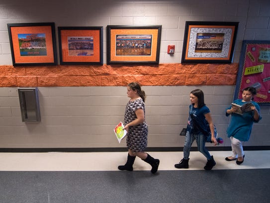 Students pass framed class pictures Thursday, Oct.