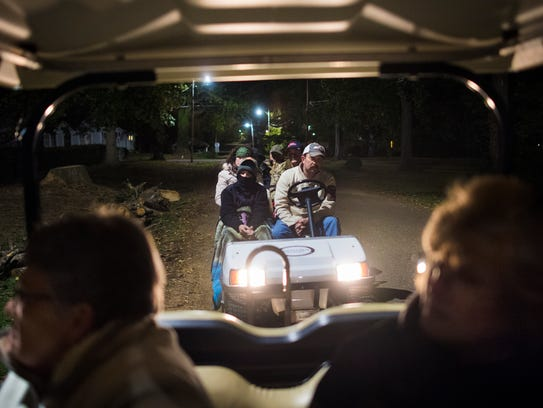 "Ghost tour attendees ride ""limo golf carts"" through"