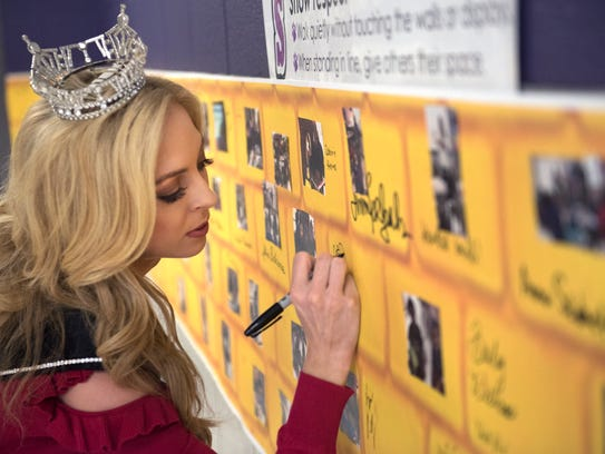 Miss Tennessee Caty Davis signs the wall of guest readers