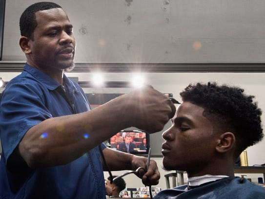 Haircuts & Shaves barbershop owner Terrance Swift trims