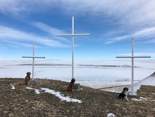Adventure dogs (from the left) Albus, Tonks and Remy sit with the crosses atop Priest Butte.
