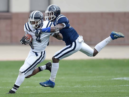 Jackson State hite team's Terrell Kennedy (4) is tackled