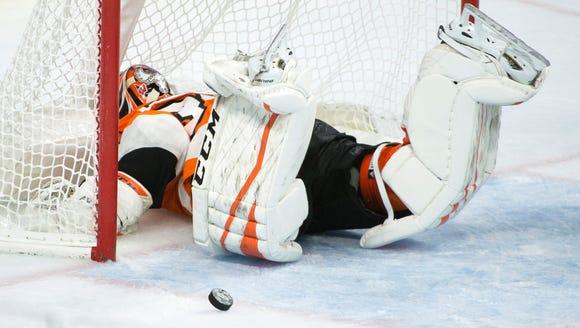 Flyers' Brian Elliott (37) slides head first into the