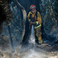 Firefighter Randy Browning hoses down a hot spot of  a fire near Pollack Pines, Calif.