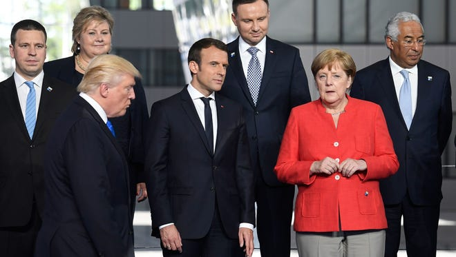 French President Emmanuel Macron and German Chancellor Angela Merkel speak as President Donald Trump arrives for a photo during the 2017 NATO summit in Brussels on May 25, 2017.
