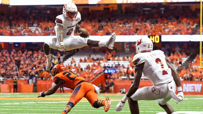 Louisville Cardinals quarterback Lamar Jackson (8) leaps over Syracuse Orange defensive back Cordell Hudson (20) during his team's 62-28 win.