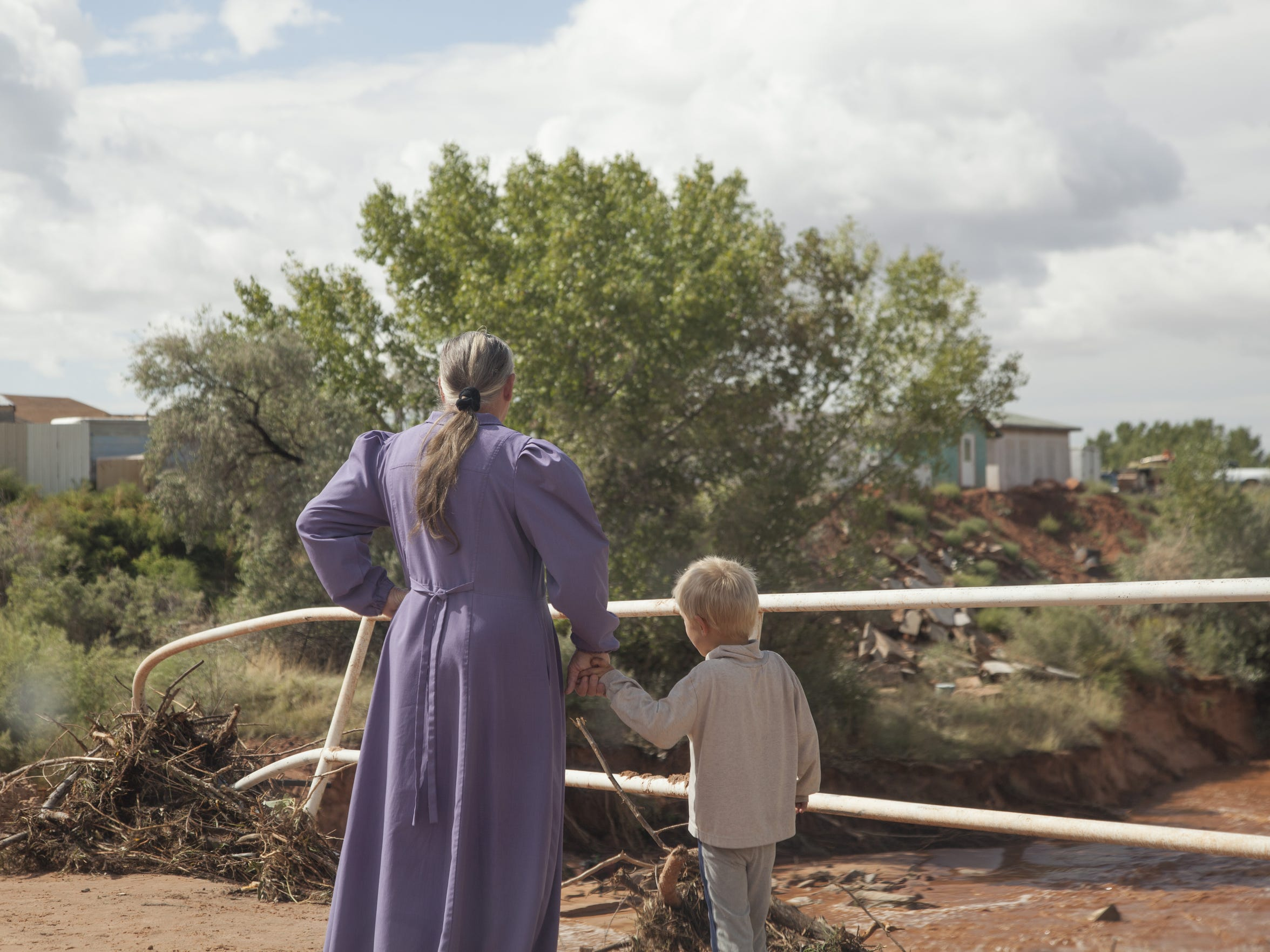 Residents of Short Creek observe damage and debris caused by a flash flood which claimed multiple lives Tuesday, Sept. 15, 2015.