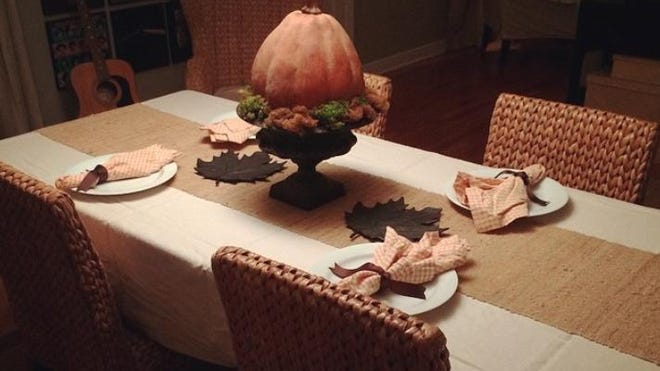 A burlap table runner gives a cozy and festive feel to your dining space.