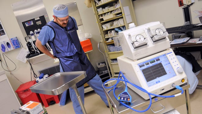 Dr. Paul Watts puts on a lead-lined apron at Hendrick Medical Center July 26, 2017 in preparation for x-raying patients while using the COOLIEF machine at right. The device employs cooled radio-frequency thermal treatment for pain relief.