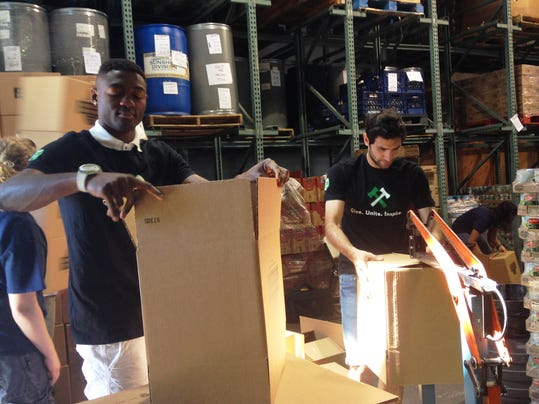 Portland Timbers forward Fanendo Adi, left, and midfielder Diego Valeri, help pack food boxes for families in need at the Portland Police Bureau's Sunshine Division as part of Stand Together Week in Portland, Oregon, on Thursday June, 19, 2014. While much of the soccer world focused on the World Cup, Nigerian striker Fanendo Adi concentrated on putting together boxes of food to donate to needy families in Portland.   (AP Photo/Anne M. Peterson)