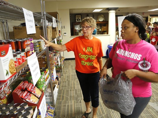 Dolores Flynn, left, assists Quiana McCalip as she selects food items at the food pantry Thursday, September 10, 2015, inside Oakland Elementary School. Oakland Elementary together with Food Finders Food Bank opened the food pantry to help feed students and their families who are struggling with food insecurity. McCalip has three children, one of whom is a fourth grade student at Oakland Elementary.