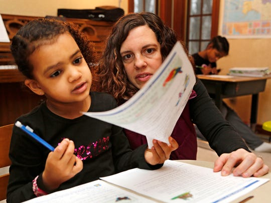Carlee Dawodu helps her daughter Keziah, 6, with capitalization Wednesday, December 17, 2014, in their Lafayette home. Dawodu has four daughters, and with a gap in their ages she prefers homeschooling as a way to keep the children together.