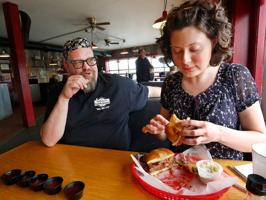 """All right Lone Star girl, how's the brisket?"" asks owner Marc Shumate as JConline arts and entertainment reporter Domenica Bongiovanni samples the Kansas City sandwich Friday, March 20, 2015, at South Street Smokehouse, 3305 South Street, No. 6, in Lafayette. The Kansas City features beef brisket with onion rings and provolone cheese served on a toasted bun. ""Does it stand up to Texas standards?"" ""I think the brisket is delicious,"" Bongiovanni said."