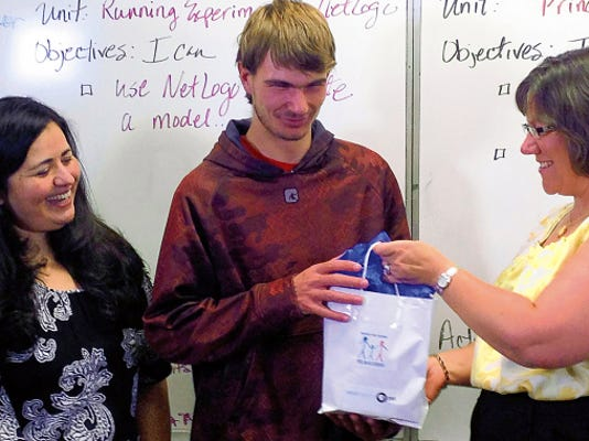 Deming High instructor for computer graphics design, Sandra Almanza, left, looks on as senior Ray Stubbs accepts his prize from Evy Stubbs (no relation) representing the New Mexico Early Learning Advisory Council and NM-PBS.