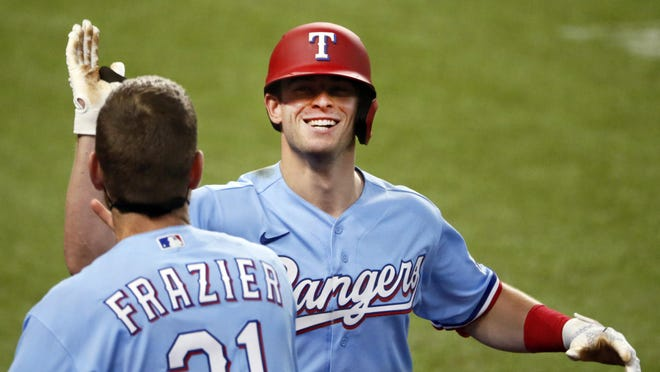 Texas Rangers' Nick Solak, right, is greeted at the dugout by Todd Frazier, left, after hitting a solo home run on a fly ball that the popped out of the mitt of Los Angeles Angels right fielder Jo Adell (not pictured) and went over the outfield wall during the fifth inning of a baseball game in Arlington, Texas, Sunday, Aug. 9, 2020.
