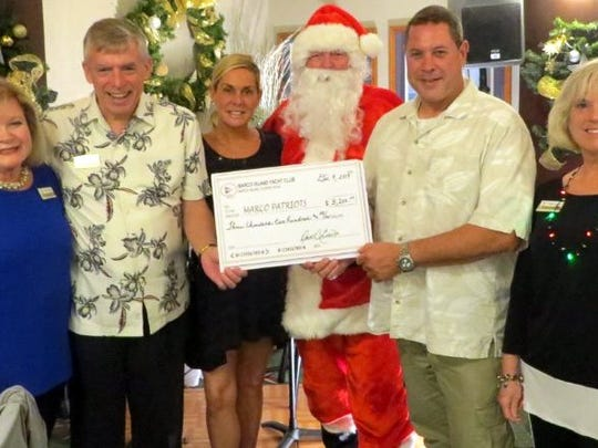Yacht Club Supports Marco Patriots: As part of its Saturday, Dec. 9 Christmas Boat Parade viewing party, the Marco Island Yacht Club raffled off a club membership that raised $3,200 for the Marco Patriots. With Santa are from left: Angela Holt, event chair; Dave Everitt, Yacht Club Chairman; Erin Mia Milchman and Matthew Melican, representatives of the Marco Patriots; and, Kathy Caruso, membership co-chair for the Yacht Club.