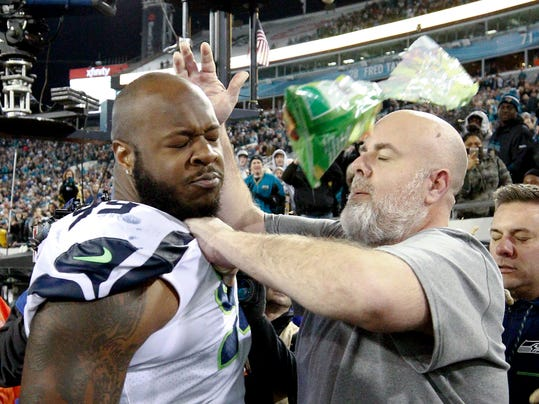 A Seattle Seahawks staff member tries to remove Seahawks defensive tackle Quinton Jefferson, left, from the field as an object thrown from the stands hits them during the closing moments of an NFL football game against the Jacksonville Jaguars, Sunday, Dec. 10, 2017, in Jacksonville, Fla. Jacksonville won 30-24. (AP Photo/Stephen B. Morton)