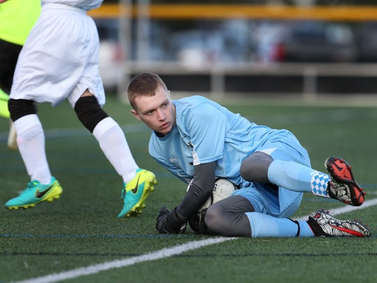 Churchville-Chili goalie, Alex Voglewede, makes a save during the Saints' soccer match against Webster Schroeder. Voglewede who missed all of last season while battling leukemia is now in remission and back in goal.