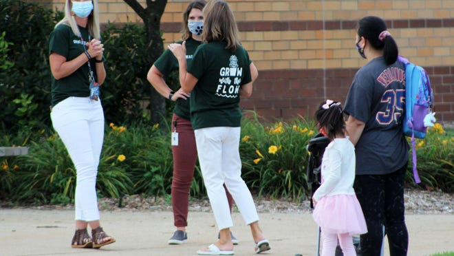 Staff at Great Lakes Elementary get ready for students to get dropped off during the first day of school on Tuesday, September 1, 2020.