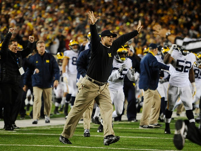 Jim Harbaugh raises his hands in victory at the end