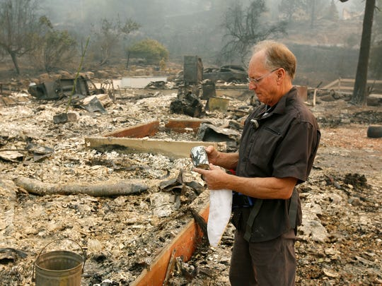 Chuck Rippey looks over a cup found in the burned out remains of his parent's home at the Silverado Resort, Tuesday, Oct. 10, 2017, in Napa, Calif. Charles Rippey, 100 and his wife Sara, 98, died when wind whipped flames swept through the area Sunday night.
