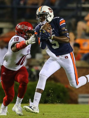 Auburn quarterback John Franklin III (5) carries the ball around Arkansas State defensive back Justin Clifton (10) during the second half of an NCAA college football game, Saturday, Sept. 10, 2016, in Auburn, Ala. (AP Photo/Butch Dill)
