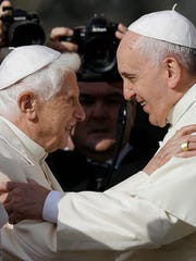 In this Sept. 28, 2014, file photo, Pope Francis, right, hugs Pope Emeritus Benedict XVI before a meeting with elderly faithful in St. Peter's Square at the Vatican.
