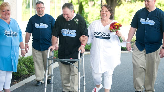 Rich Myers, center left, a beloved figure throughout Haddon Township for his dedication to the community, walks with his new wife, Kimberly Pierce after their wedding ceremony at the Kove in Audubon on Saturday.  Myers, a longtime Haddon Township baseball coach and umpire, is battling ALS.